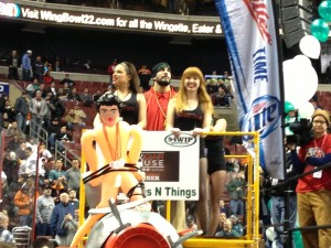 "Dave ""DJ"" Brunelli enters on the first float of Wing Bowl 22 last Friday. A mock broadcast booth, the rubber doll affixed to a cannon was his entourage's ""goodbye"" to Chris Wheeler. -photo by Joe Darrah"